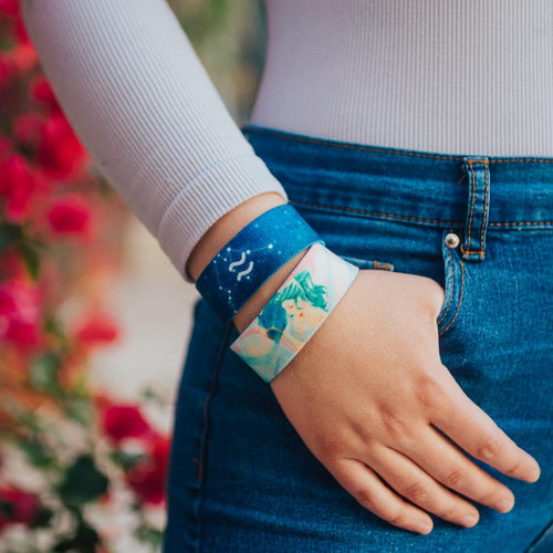 Lifestyle close up image of model's hand in their pocket and wearing two Aquarius straps