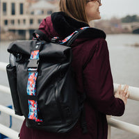 lifestyle photo of the Imperial v2 with a different colored tension and closure straps on a woman's shoulders while looking towards a body of water
