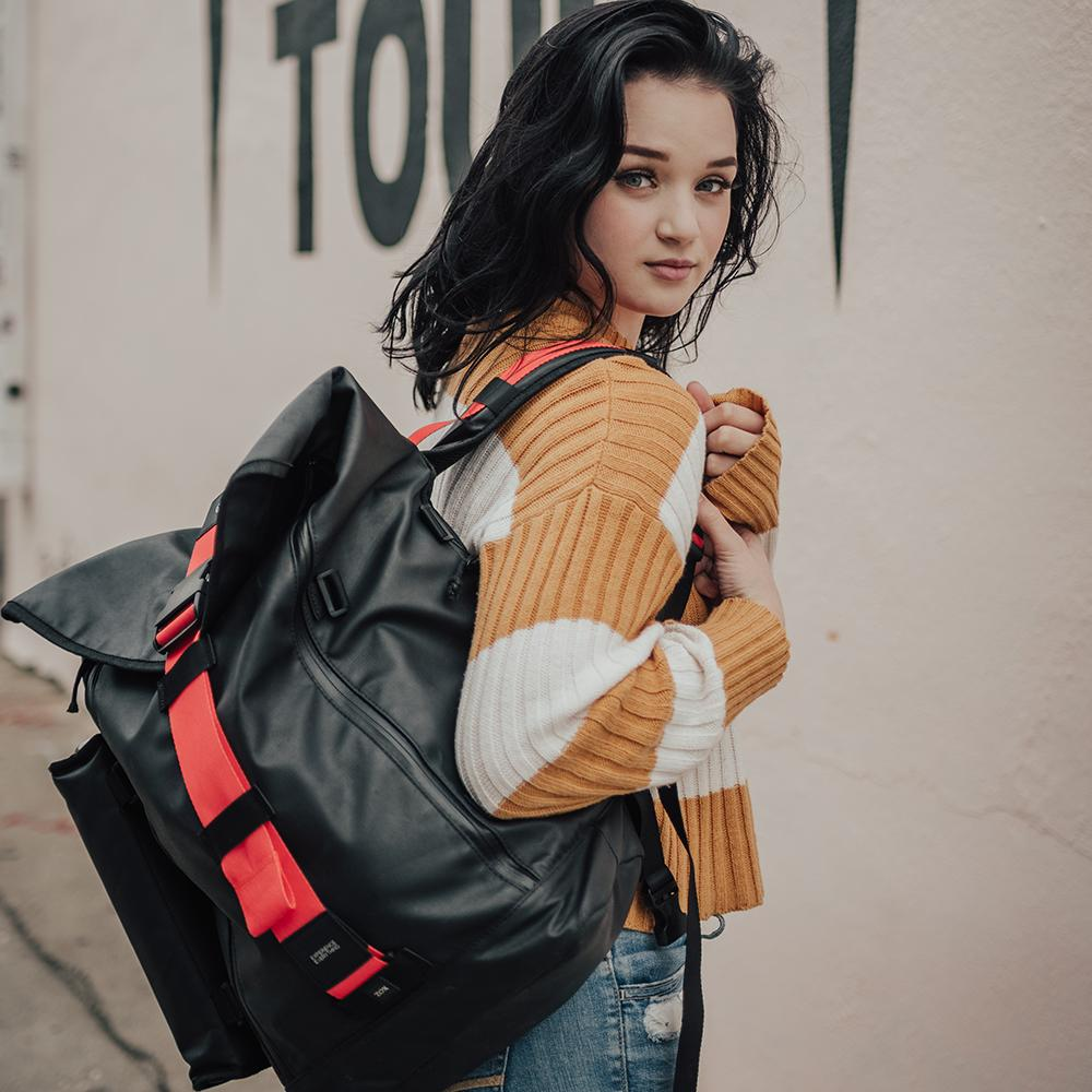 lifestyle photo of the Imperial v2 with a different colored closure strap on a woman's shoulder while looking back at the camera