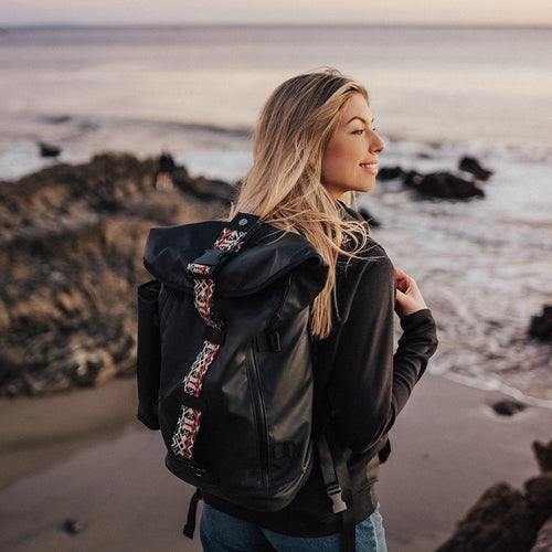 lifestyle photo of the Imperial v2 with a different colored closure strap on a woman's shoulders while at the beach
