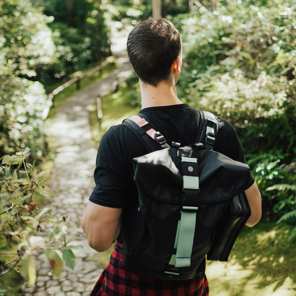 lifestyle photo of the Imperial v2 with a different colored tension and closure strap on a mans shoulders while hiking