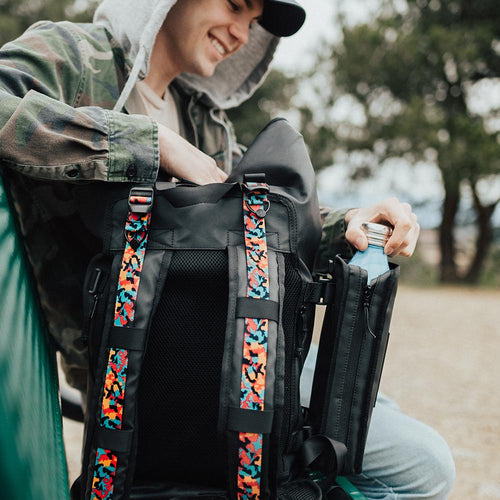 a man sitting down next to the imperial v2 backpack with the front showing so you are able to see the different tension straps that he has put in the bag, he is grabbing his water bottle from the water capsule that is attached to the bag.