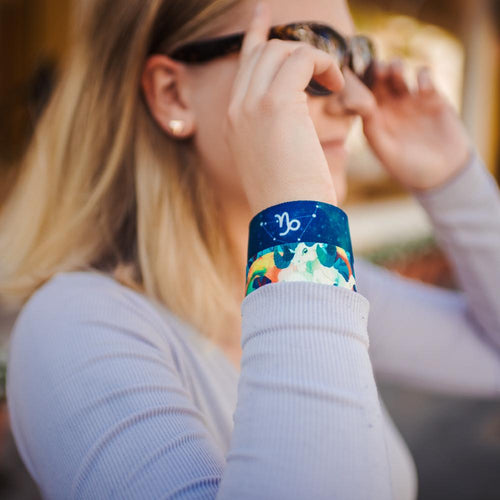 Lifestyle close up image of model putting on sunglasses and wearing two Capricorn straps