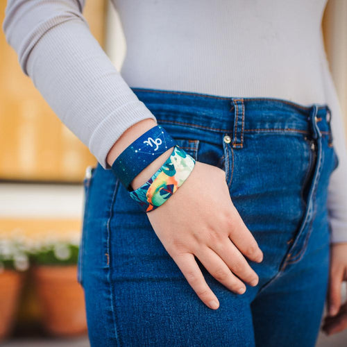 Lifestyle close up image of model's hand in their pocket and wearing two Capricorn straps