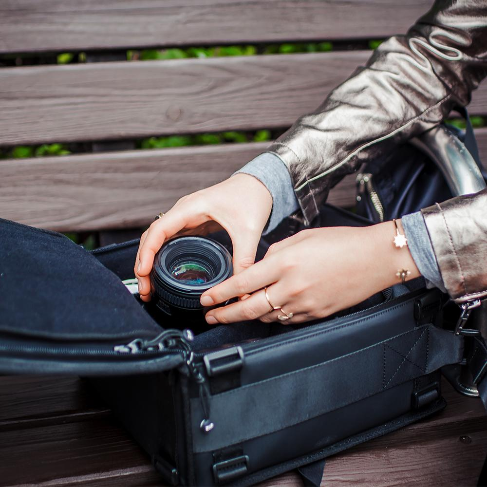 a lifestyle image showing a woman removing a lens from an opened up camera bag