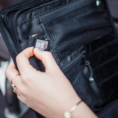 A woman removing an SD card from an opened camera bag which shows multiple little pockets for extra gear
