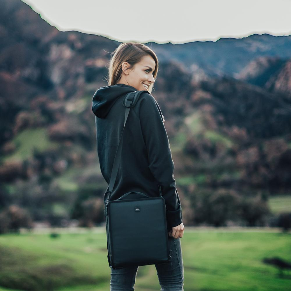 a lifestyle image of a girl standing with the camera bag hanging from her shoulder overlooking the mountains.