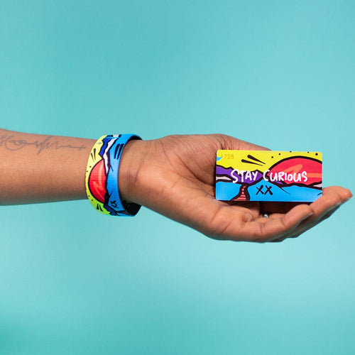 Studio Image of hand holding card that says Stay Curious with a Stay Curious strap on their wrist