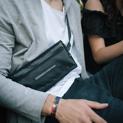 lifestyle photo of a man wearing the fanny pack cross body while sitting next to a woman