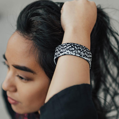 Studio image close up of Do on wrist of someone with their hand in their hair