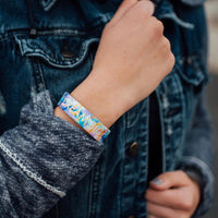 Lifestyle photo up close of wrist while wearing dream big single showing inside design with dream big in bold text with blue, purple, and yellow watercolored background