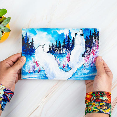 Studio image for outside of the custom envelope for the Fairies Pack held in hands that have two straps on each wrist from the pack. Design of the outside envelop is of a winter scene with a blue sky, trees, a few pink flowers, and a close up from behind of a sitting white fox