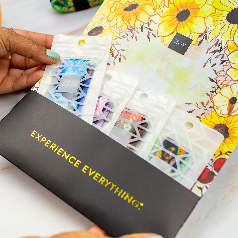 Studio Image of Fairies Pack in custom envelope. Top flap of envelope has Zox logo in the middle with illustrated sunflowers around it. On the bottom pocket of the envelope, that holds the Fairies Pack in their individual white bags, it says Experience Everything in gold reflective coloring