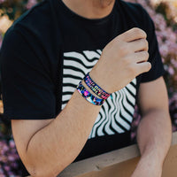 Lifestyle photo of guy wearing two find bigger problems singles one showing the inside design with bold text find bigger problems in a pink to yellow gradient with transparent neon geometric designs overlaying a black background above the single showing the outside design of find bigger problems with neon geometric design overlaying a black background