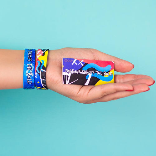 Studio photo of hand holding number-matching collector's card in front of bright blue background showing two fortune favors the bold singles one showing the outside design with hand drawn abstract art above another single with the inside design showing a bold white text fortune favors the bold with hand drawn abstract art