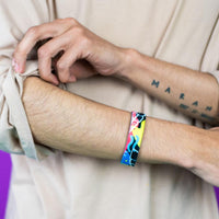 Studio photo of guy rolling up sleeve wearing fortune favors the bold single showing the outside design with hand drawn abstract art