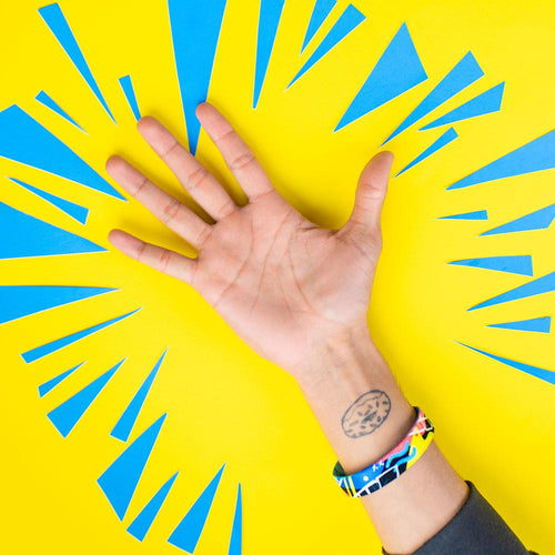 Studio photo of wrist in front of bright yellow background of fortune favors the bold single showing the outside design with hand drawn abstract art