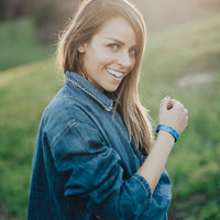 Lifestyle image close up of someone smiling with Give Thanks on their wrist