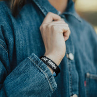 Lifestyle image close up of Give Thanks on model's wrist