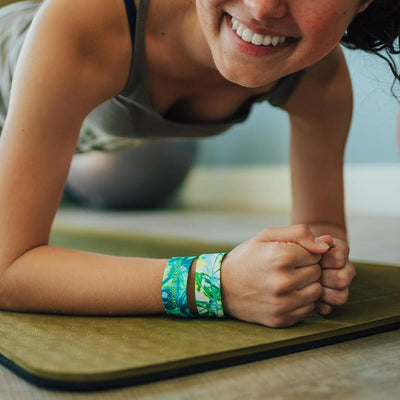Lifestyle close up of someone holding plank exercise position with 2 Grow Every Day on wrist