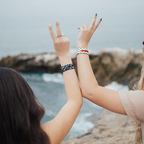Lifestyle image of two arms raised up next to each other giving the peace sign with hands while each wearing a Good Vibes Only strap