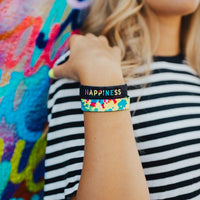 Lifestyle photo up close of a girl's wrist showing the inside and outside design of the happiness single