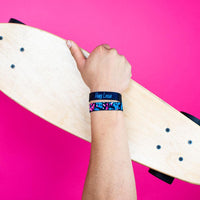Studio photo of guy holding a skateboard wearing two hang loose singles one with the outside design of neon tropical flower print overlaying black background and below the other showing the inside design of hang loose with italic text hang loose with grey and black striped background