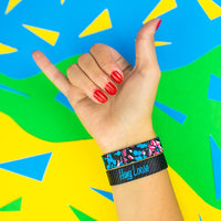Studio photo of hand signing hang loose showing wrist wearing two hang loose singles one with the outside design of neon tropical flower print overlaying black background and above the other showing the inside design of hang loose with italic text hang loose with grey and black striped background
