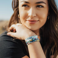Lifestyle image of Happy To Be Here on wrist of smiling model