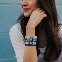 Lifestyle image of 2 Happy To Be Here on wrist of smiling model