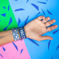 Studio Image of 2 Hug It Out on a wrist in front of a colorful background