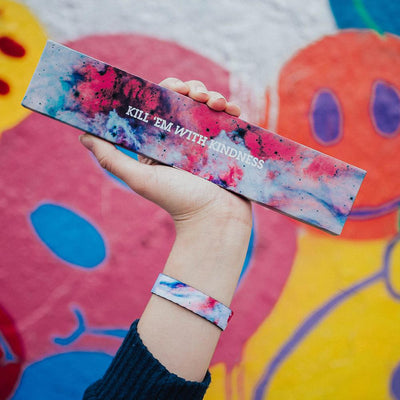 Lifestyle image of a hand holding a colorful box that says Kill 'Em With Kindness and wearing the Kill 'Em With Kindness imperial
