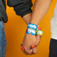 Studio image close up of couple holding hands each wearing 2 Lovebird wristbands