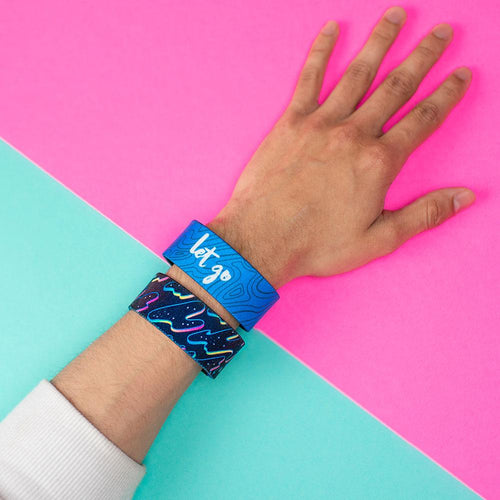 Studio Image of 2 Let Go on a wrist in front of a pink and teal background