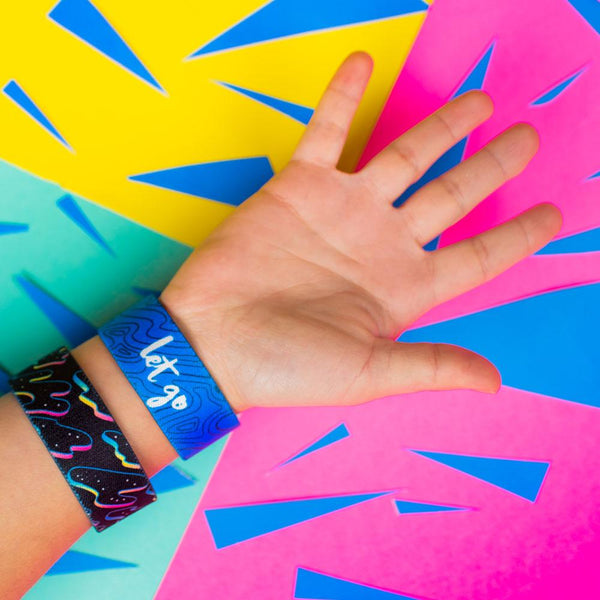 Studio Image of 2 Let Go on a wrist in front of a colorful background