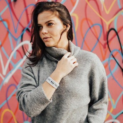 Lifestyle image of a woman in front of a colorful background wearing a grey sweatshirt and Love Who You Are on her wrist
