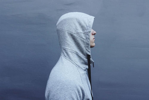 a young males side profile while wearing a lunar grey zip imperial hoodie with the hood up