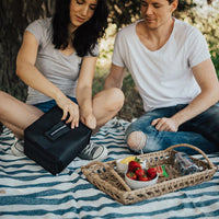 couple on a blanket opening the lunch box to remove food from it