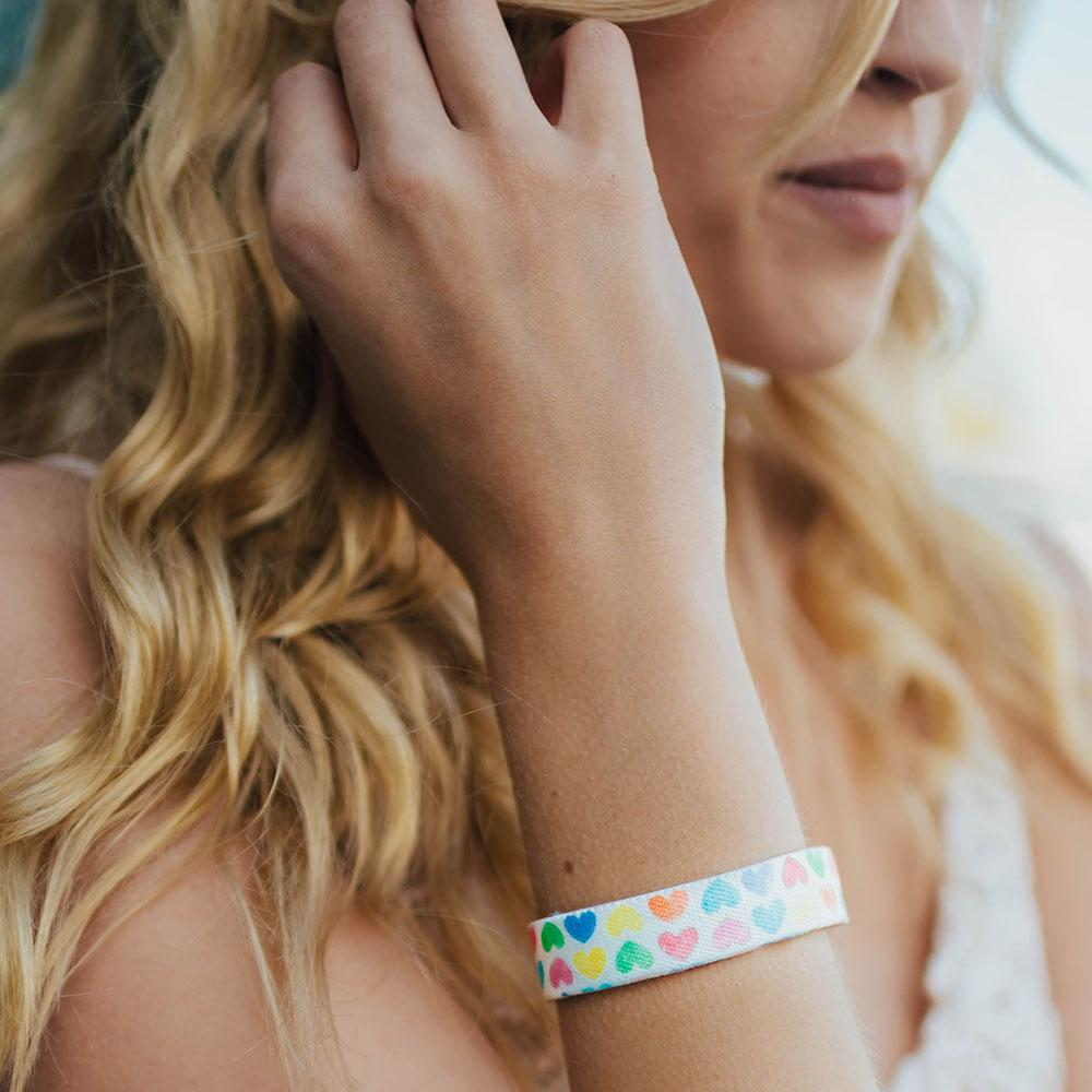 Lifestyle photo up close of girl showing wrist with live with love single showing the outside design of with rows of pastel orange, yellow, pink, green, purple, and blue gradient hearts over white background