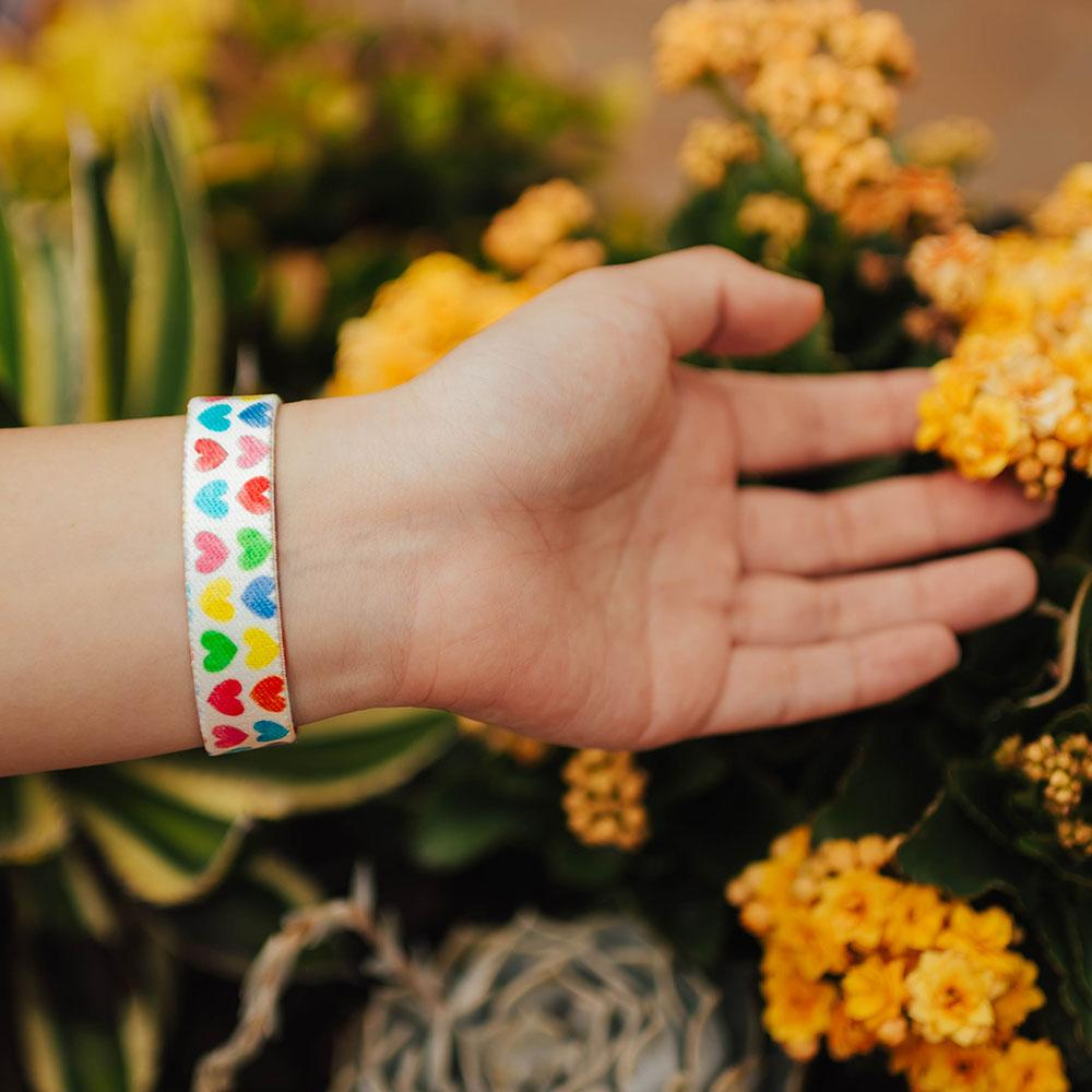 Lifestyle photo of hand reaching for flowers showing wrist with live with love single showing the outside design of with rows of pastel orange, yellow, pink, green, purple, and blue gradient hearts over white background