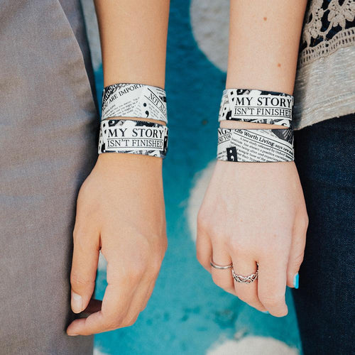 Lifestyle image close up image of two wrists both wearing 2 My Story Isn't Finished straps