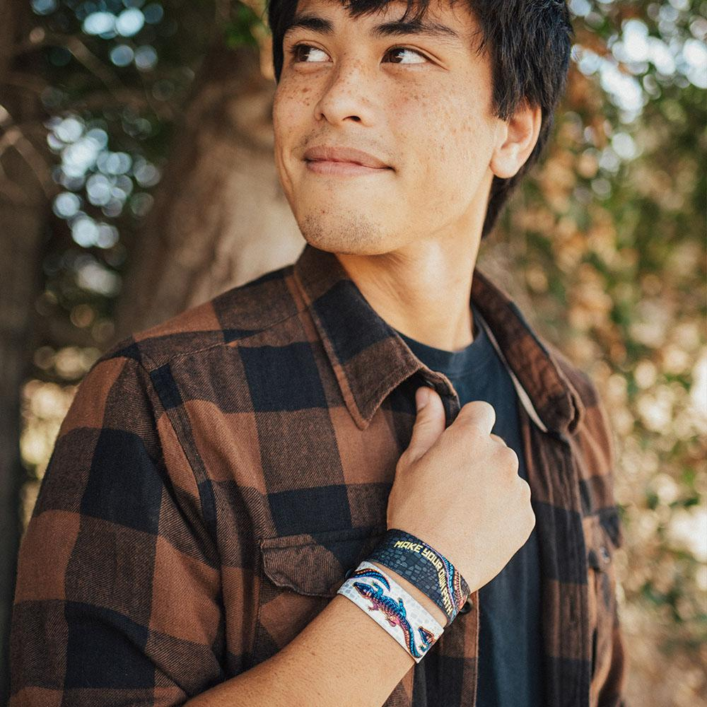 lifestyle image of a man holding his plaid shirt collar wearing two Make your own path wristbands. One showing the inside design and the other showing the outside.