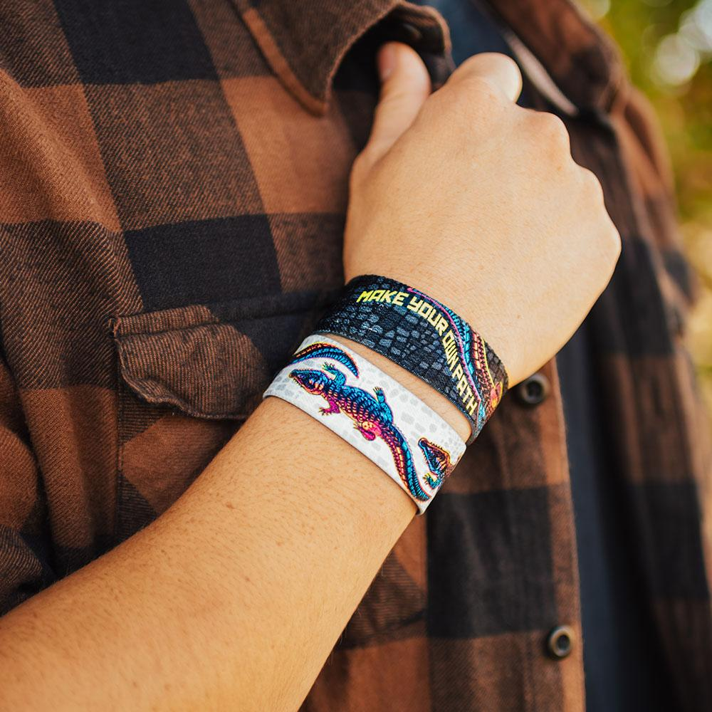 lifestyle image of a hand holding a plaid shirt wearing two Make your own path wristbands. One showing the inside design and the other showing the outside.