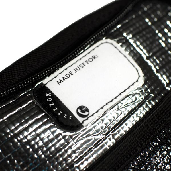 A detail image showing the tag of the smaller backpack where you are able to put the name of who owns the backpack