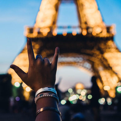 Lifestyle close up image of a hand in front of the Eiffel Tower wearing Never Give Up