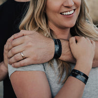 Lifestyle image of women being hugged from behind. Person behind her is wearing No Mountain High Enough and she is wearing No Valley Low Enough