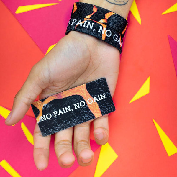 Studio photo of hand holding the number-matching collector's card while wearing two no pain, no gain singles showing the inside and outside design