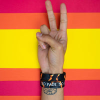 Studio photo of a hand signing a peace sign in front a bright colored background showing the inside and outside design of the no pain, no gain single