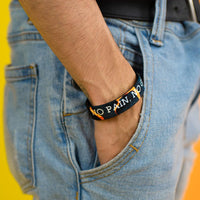 Studio photo of guy with hand in jean pocket showing the inside design of no pain, no pain a white bold text overlaying a black and orange poison dart frog design