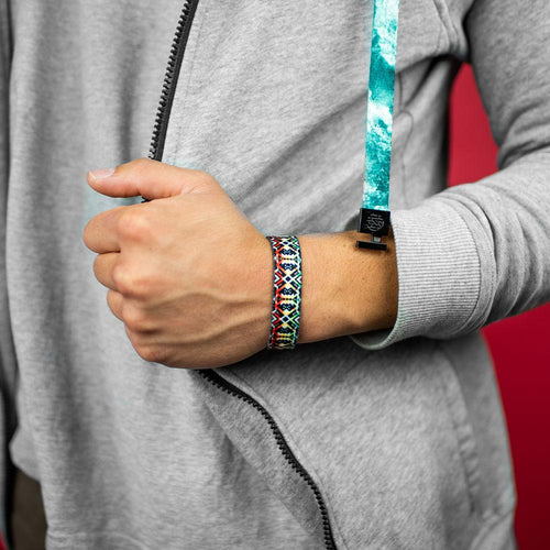 Studio photo close up on the wrist of a guy wearing a ZOX hoodie showing the outside design of never surrender